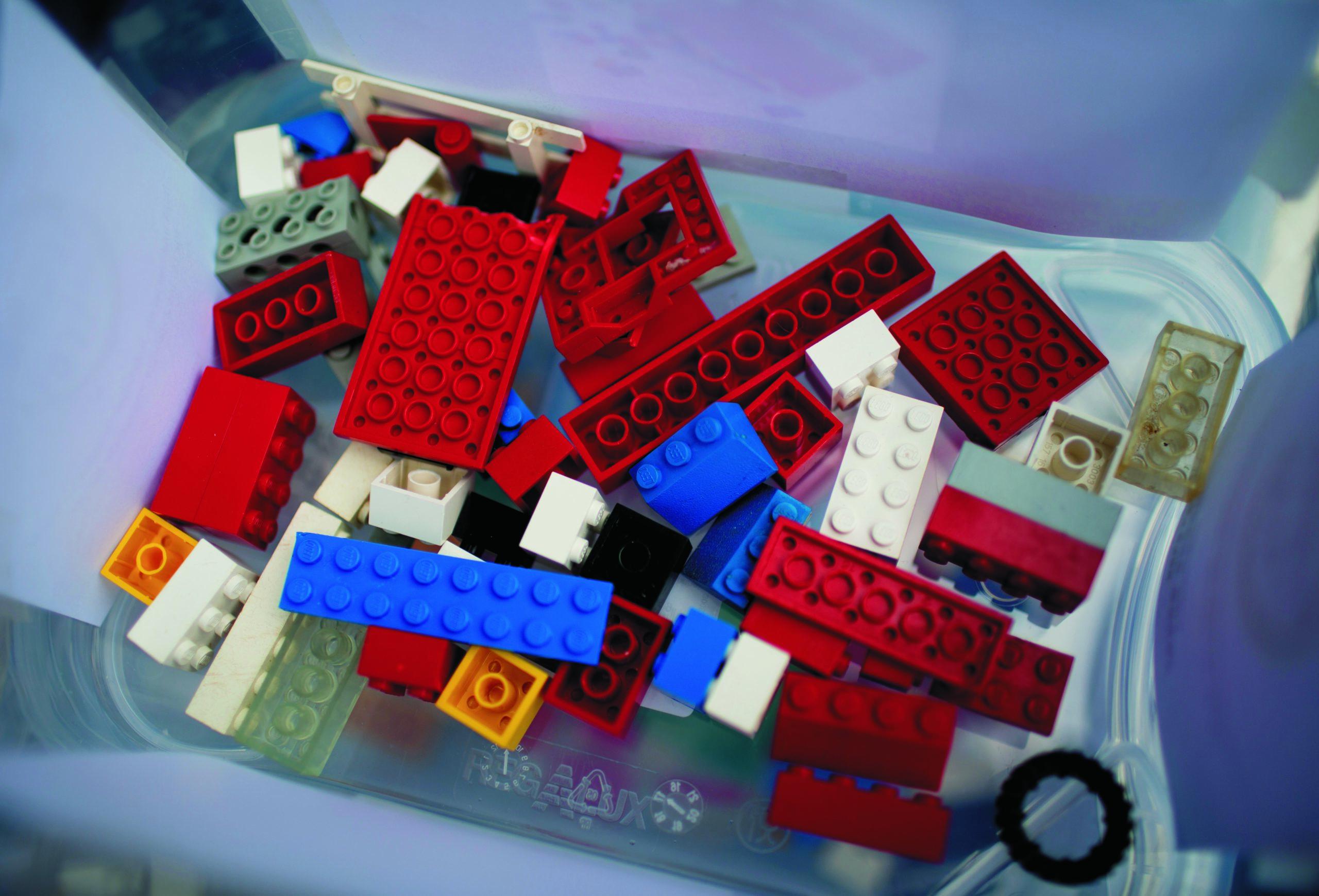 Der Blick in eine transparente Kiste von oben. Am Boden der Kiste befinden sich einige wenige bunte Legosteine.