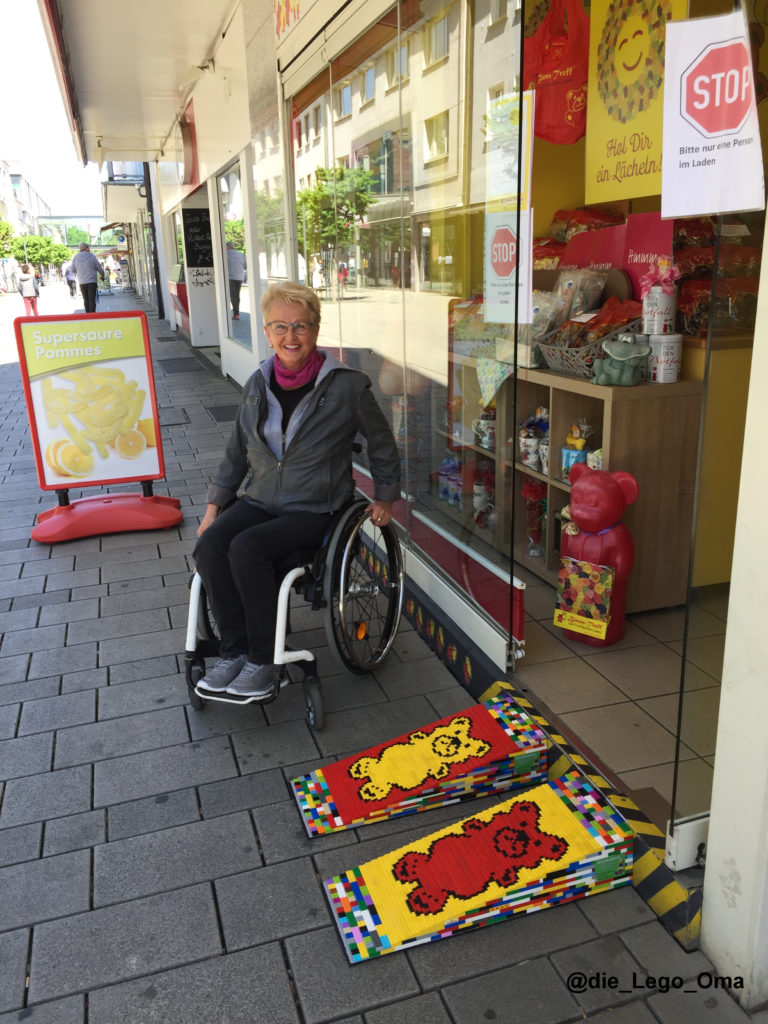 Eine Frau sitzt im Rollstuhl vor dem Bärentreff. Der Laden hat eine Lego-Rampe im Bären Design.